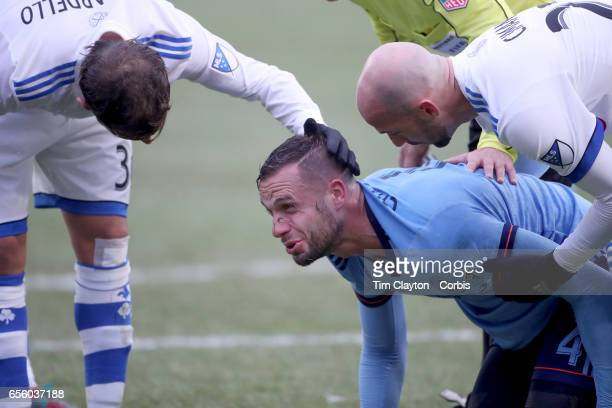 Maxime Chanot of New York City FC is consoled by Laurent Ciman of Montreal Impact and Hernan Bernardello of Montreal Impact during the New York City...