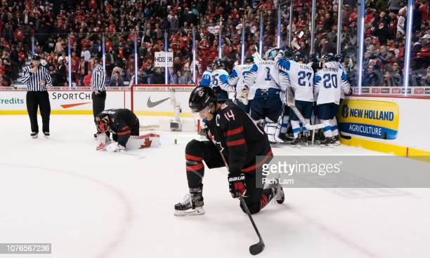 Maxime Comtois and goalie Michael Dipietro of Canada kneels on the ice as Finland celebrates after winning 21 in overtime in Quarterfinal hockey...