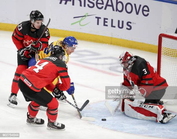 Maxime Comtois of Canada defends against Oskar Steen of Sweden with Carter Hart of Canada defending his net during the first period of play in the...