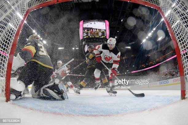 Maxime Lagace of the Vegas Golden Knights tends net against Miles Wood of the New Jersey Devils during the game at TMobile Arena on March 14 2018 in...