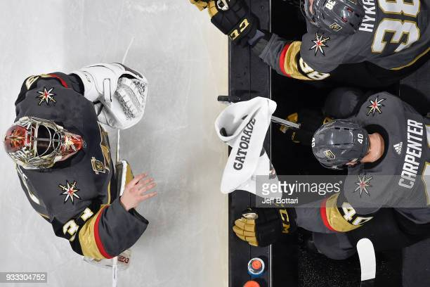 Maxime Lagace tosses a towel to teammate Ryan Carpenter of the Vegas Golden Knights during a break in the game against the New Jersey Devils at...