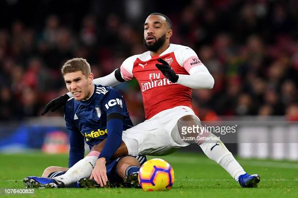 Maxime Le Marchand of Fulham tackles Alexandre Lacazette of Arsenal during the Premier League match between Arsenal FC and Fulham FC at Emirates...