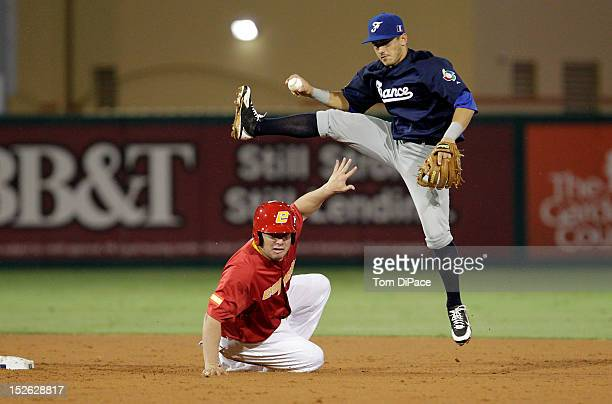 Maxime Lefevre of Team France jumps to avoid a sliding Rafael Alvarez of Team Spain during game 2 of the Qualifying Round of the 2013 World Baseball...