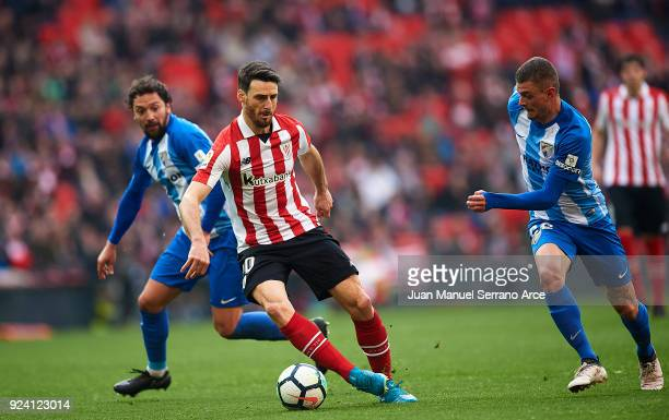 Maxime Lestienne of Malaga CF competes for the ball with Aritz Aduriz of Athletic Club during the La Liga match between Athletic Club Bilbao and...