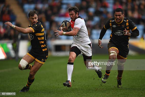Maxime Medard of Toulouse makes a break between Josh Bassett and Nathan Hughes of Wasps during the European Rugby Champions Cup Pool 2 Round 5 match...