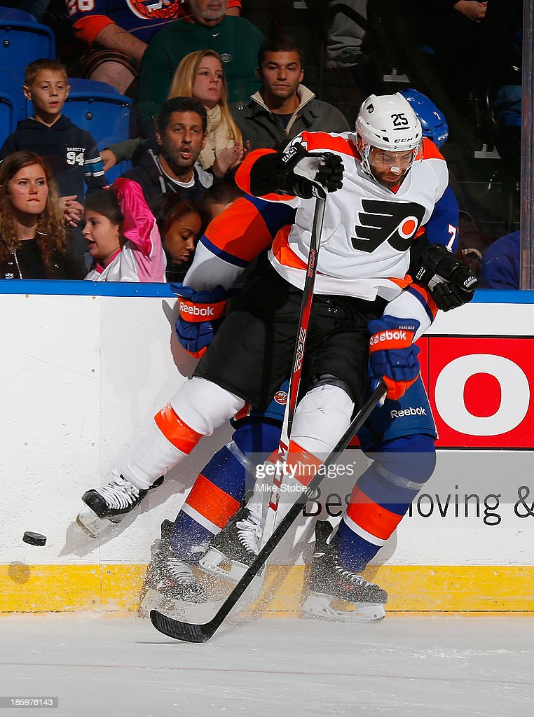 Maxime Talbot #25 of the Philadelphia Flyers battles for the puck with Matt Carkner #7 of the New York Islanders at Nassau Veterans Memorial Coliseum on October 26, 2013 in Uniondale, New York. The Flyers defeated the Islanders 5-2.