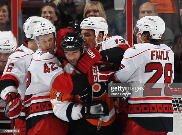 Maxime Talbot of the Philadelphia Flyers is held by Brett Sutter Anthony Stewart and Justin Faulk of the Carolina Hurricanes at the Wells Fargo...