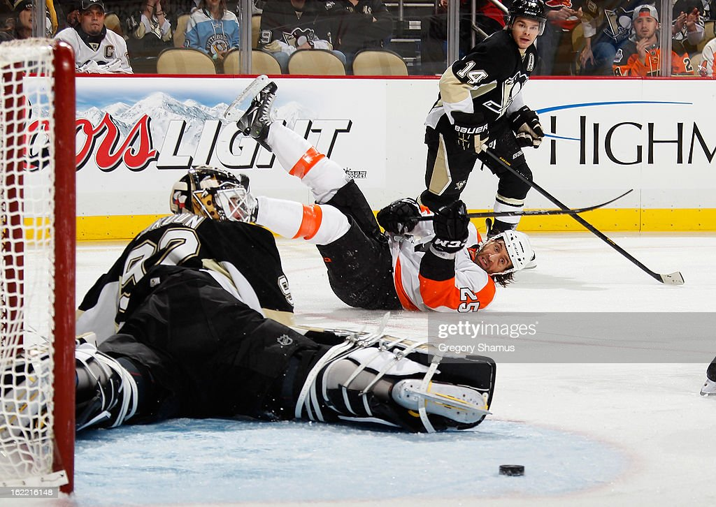 Maxime Talbot #25 of the Philadelphia Flyers takes a diving shot between Tomas Vokoun #92 and Chris Kunitz #14 of the Pittsburgh Penguins on February 20, 2013 at Consol Energy Center in Pittsburgh, Pennsylvania.