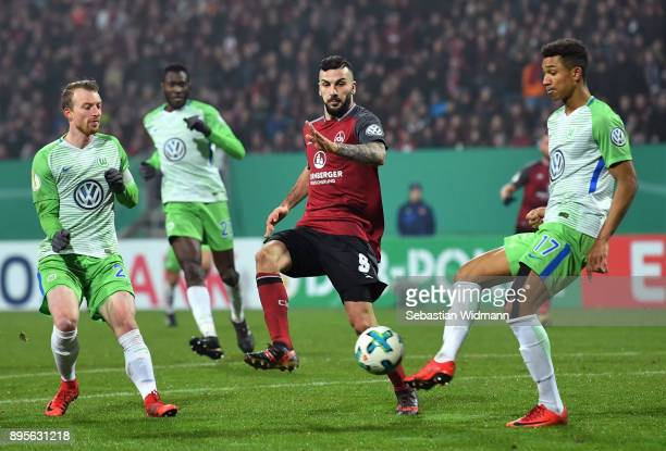 Maximilian Arnold and Felix Uduokhai of Wolfsburg compete with Mikael Ishak of Nuernberg for the ball during the DFB Cup match between 1 FC Nuernberg...