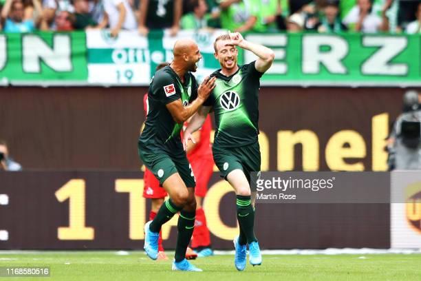 Maximilian Arnold of VfL Wolfsburg celebrates with teammate John Anthony Brooks after scoring the opening goal during the Bundesliga match between...