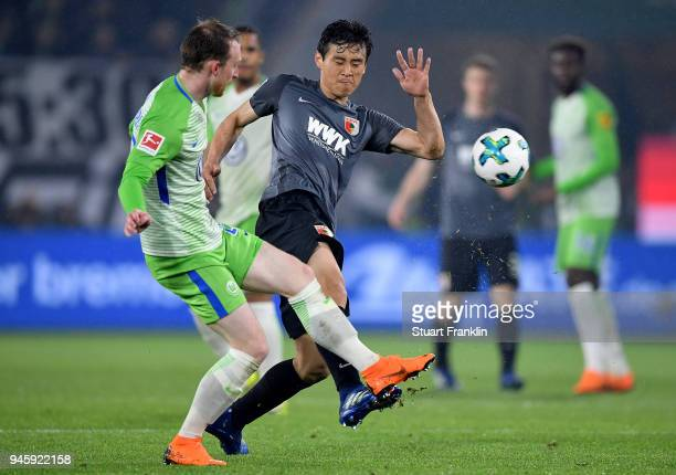 Maximilian Arnold of Wolfsburg and Ja Cheol Koo of Augsburg battle for the ball during the Bundesliga match between VfL Wolfsburg and FC Augsburg at...