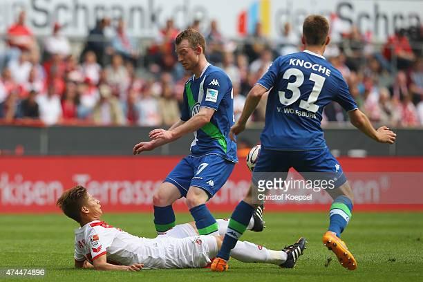Maximilian Arnold of Wolfsburg and Robin Knoche of Wolfsburg challenge Kazuki Nagasawa of Koeln during the Bundesliga match between 1 FC Koelan and...