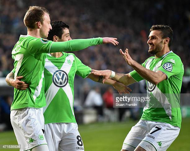 Maximilian Arnold of Wolfsburg celebrates with his teammates Freitas DeVieirinha of Wolfsburg and Daniel Caligiuri of Wolfsburg after scoring his...