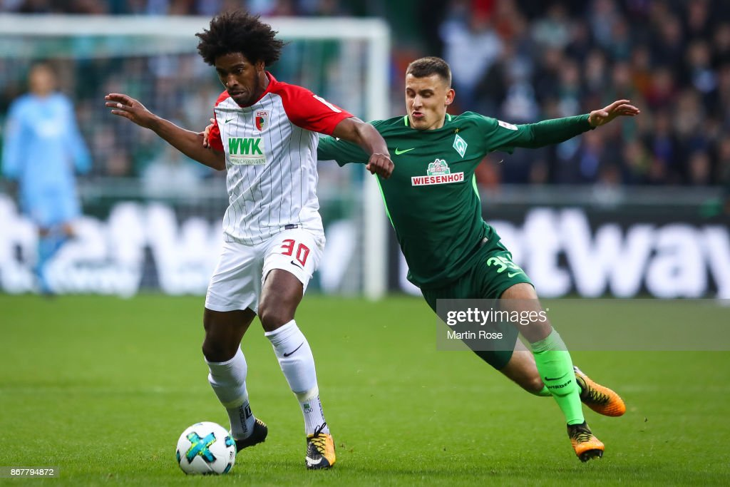 Maximilian Eggestein of Bremen (R) and Caiuby of Augsburg battle for the ball during the Bundesliga match between SV Werder Bremen and FC Augsburg at Weserstadion on October 29, 2017 in Bremen, Germany.