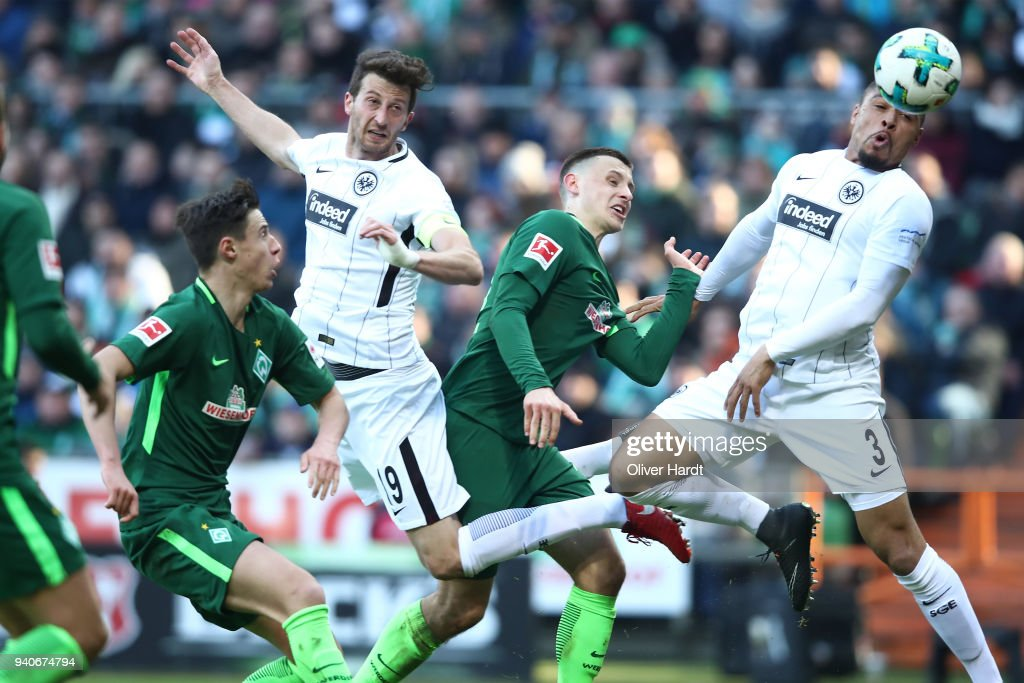 Maximilian Eggestein (C) of Bremen and David Abraham and Simon Falette (L-R) of Frankfurt compete for the ball during the Bundesliga match between SV Werder Bremen and Eintracht Frankfurt at Weserstadion on April 1, 2018 in Bremen, Germany.
