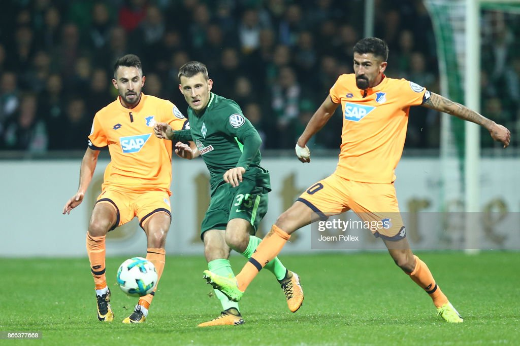 Maximilian Eggestein (M) of Bremen and Kerem Demirbay (R) and Lukas Rupp of Hoffenheim compete for the ball during the DFB Cup match between Werder Bremen and 1899 Hoffenheim at Weserstadion on October 25, 2017 in Bremen, Germany.