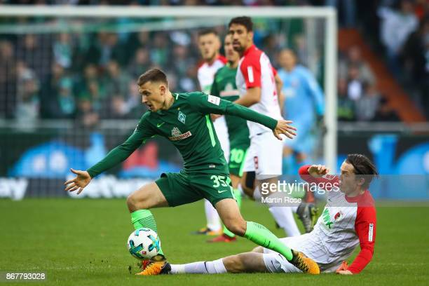 Maximilian Eggestein of Bremen and Michael Gregoritsch of Augsburg battle for the ball during the Bundesliga match between SV Werder Bremen and FC...