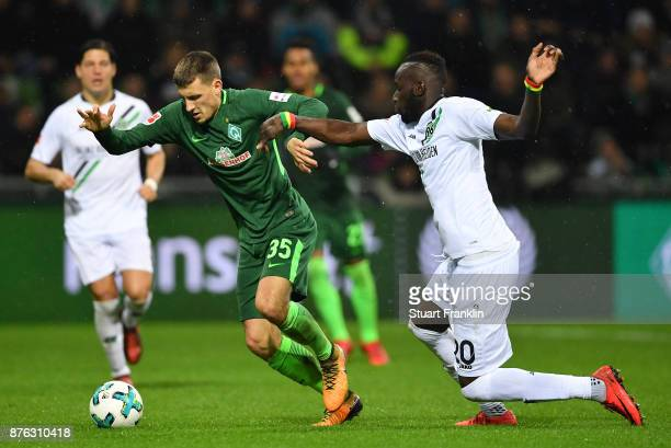 Maximilian Eggestein of Bremen is challenged by Salif Sane of Hannover during the Bundesliga match between SV Werder Bremen and Hannover 96 at...