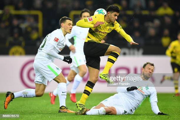 Maximilian Eggestein of Bremen watches Mahmoud Dahoud of Dortmund as he is fouled by Philipp Bargfrede of Bremen during the Bundesliga match between...