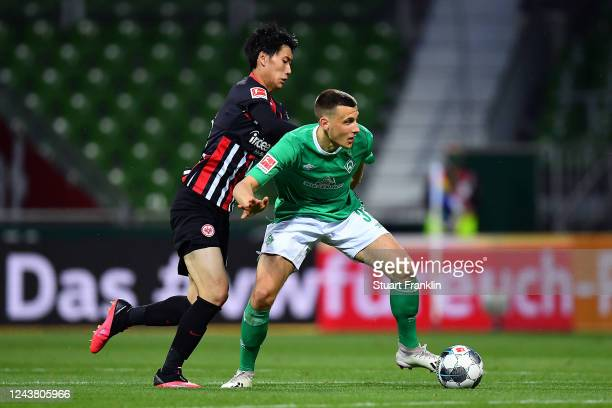 Maximilian Eggestein of SV Werder Bremen is tackled by Daichi Kamada of Eintracht Frankfurt during the Bundesliga match between SV Werder Bremen and...