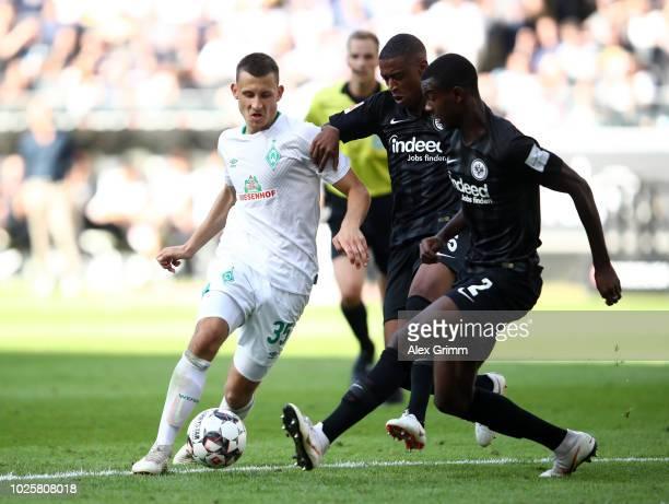 Maximilian Eggestein of Werder Bremen battles for possession with Gelson Fernandes of Eintracht Frankfurt and Evan Obite Ndicka of Eintracht...
