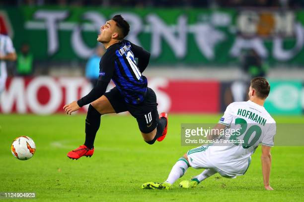 Maximilian Hofmann of SK Rapid Wien fouls Lautaro Martinez of FC Internazionale during the UEFA Europa League Round of 32 First Leg match between SK...