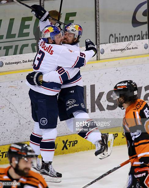 Maximilian Kastner of Muenchen jubilates with team mate Daniel Sparre after scoring his teams third goal during the DEL playoffs final game four...