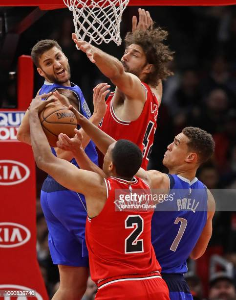 Maximilian Kleber and Dwight Powell of the Dallas Mavericks battle for a rebound with Robin Lopez and Jabari Parker of the Chicago Bulls at the...