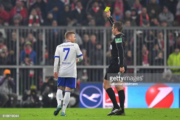 Maximilian Meyer of Schalke is shown a yellow card by referee Tobias Stieler during the Bundesliga match between FC Bayern Muenchen and FC Schalke 04...