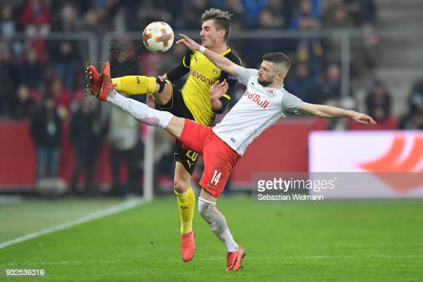 Maximilian Philipp of Dortmund and Valon Berisha of Salzburg compete for the ball during the UEFA Europa League Round of 16 2nd leg match between FC...