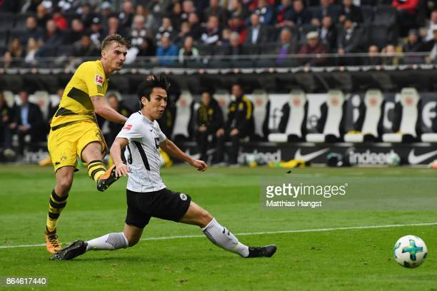 Maximilian Philipp of Dortmund shots past Makoto Hasebe of Frankfurt to score his teams second goal to make it 20 during the Bundesliga match between...