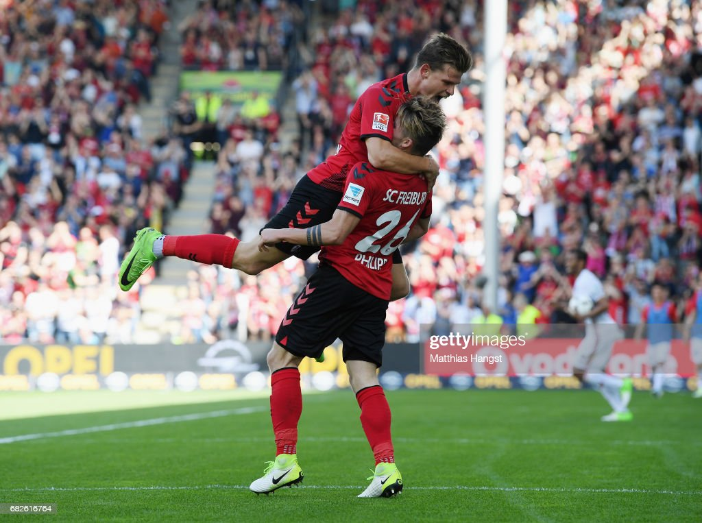 Maximilian Philipp of Freiburg celebrates with his team-mate Florian Niederlechner of Freiburg after scoring his team's first goal during the Bundesliga match between SC Freiburg and FC Ingolstadt 04 at Schwarzwald-Stadion on May 13, 2017 in Freiburg im Breisgau, Germany.
