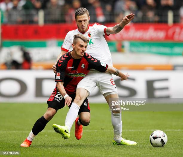 Maximilian Philipp of Freiburg is challenged by Jeffrey Gouweleeuw of Augsburg during the Bundesliga match between FC Augsburg and SC Freiburg at WWK...