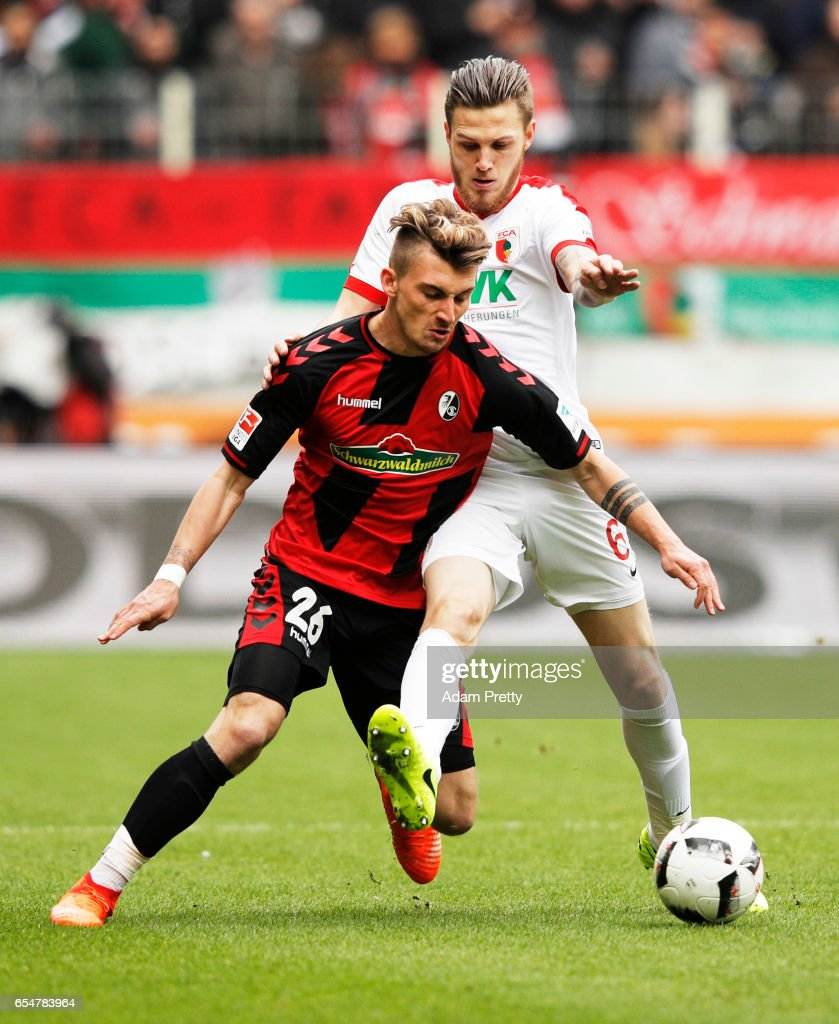 Maximilian Philipp of Freiburg is challenged by Jeffrey Gouweleeuw of Augsburg during the Bundesliga match between FC Augsburg and SC Freiburg at WWK Arena on March 18, 2017 in Augsburg, Germany.