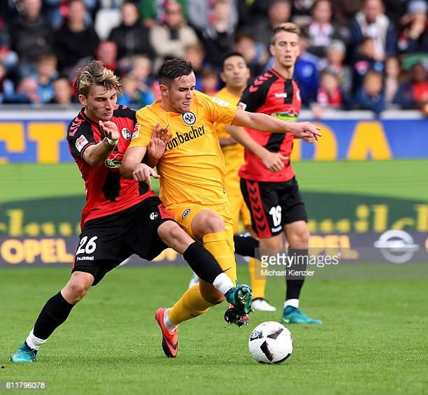 Maximilian Philipp of SC Freiburg challenges Shani Tarashaj of Eintracht Frankfurt during the Bundesliga match between Sport Club Freiburg and...