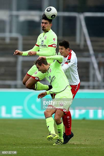 Maximilian Rossmann of Mainz Mattti Seinmann of Mainz and Markus Pazurek of Fortuna Koeln go up for a header during the Third League match between...