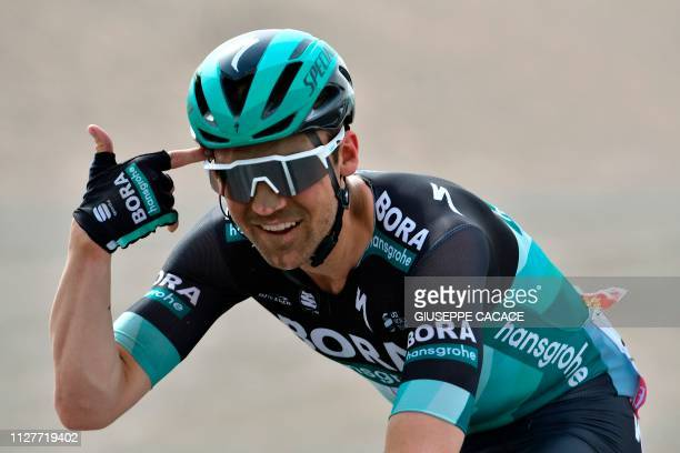 Maximilian Schachmann Germany rider for Bora Hansgrohe gestures while he rides in a sand storm during the fourth stage of the UAE cycling tour in...