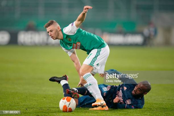 Maximilian Ullmann of Rapid Vienna looks to break past Alexandre Lacazette of Arsenal during the UEFA Europa League Group B stage match between Rapid...