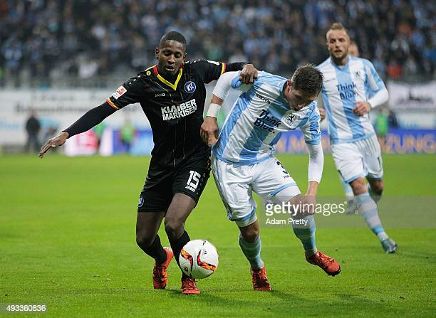Maximilian Wittek of TSV 1860 Munich is challenged by Boubacar Barry of Karlsruher SC during the 2 Bundesliga match between 1860 Muenchen and...