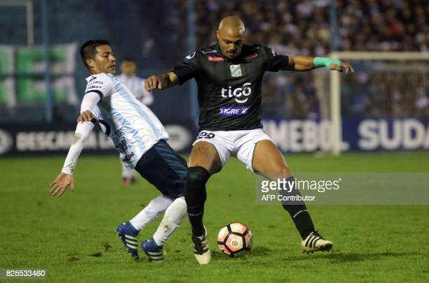 Maximiliano Freitas of Bolivia's Oriente Petrolero is marked by Guillermo Acosta of Argentina's Atletico Tucuman during a Copa Sudamericana football...