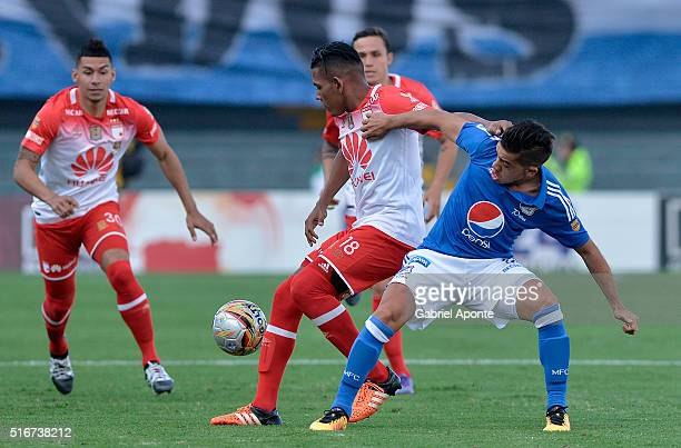 Maximiliano Nuñez of Millonarios struggles for the ball with Almir Soto of Santa Fe during a match between Millonaris and Santa Fe as part of 10th...