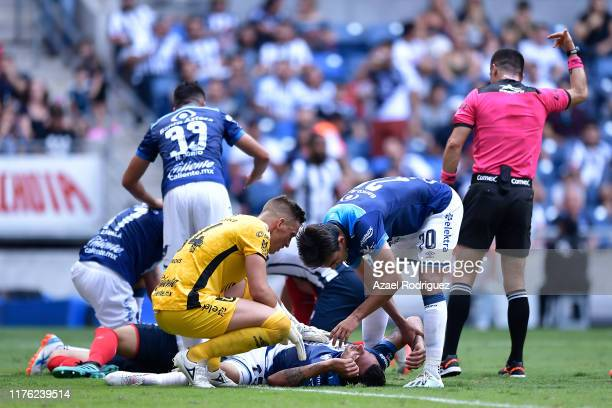 Maximiliano Perg #25 of Puebla lies on the ground after being injured while fighting for the ball with César Montes #3 of Monterrey during the 10th...