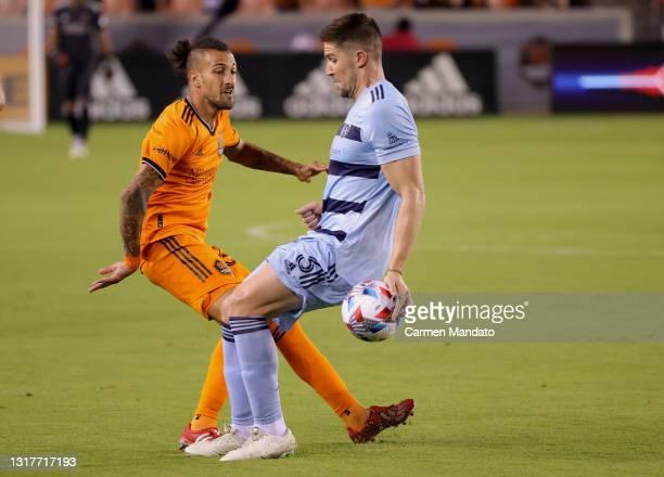 Maximiliano Urruti of Houston Dynamo battles for ball control against Andreu Fontas of Sporting Kansas City during the second half at BBVA Stadium on...