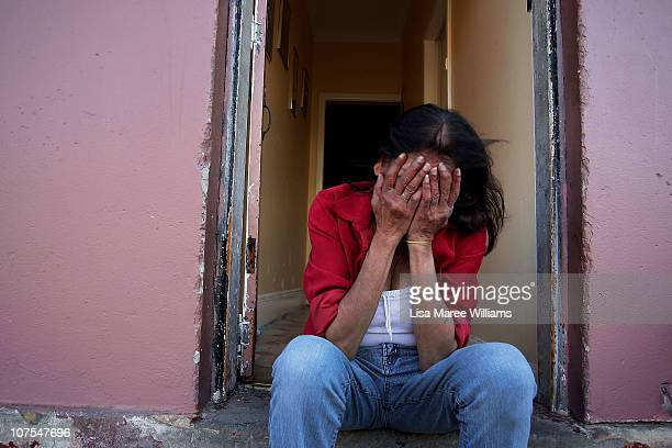 """Maxine puts her face in her hands as she sits on a friends doorstep in Vine Street in the Aboriginal housing community known as """"The Block"""" in..."""