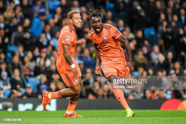 Maxwel Cornet of Lyon celebrates his goal with Memphis Depay during the Champions League match between Manchester City and Lyon at Etihad Stadium on...
