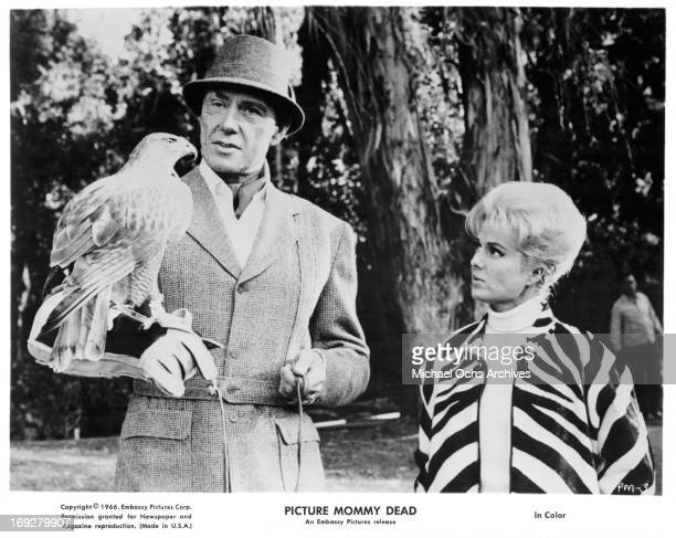 Maxwell Reed holds a falcon with Martha Hyer in a scene from the film 'Picture Mommy Dead' 1966