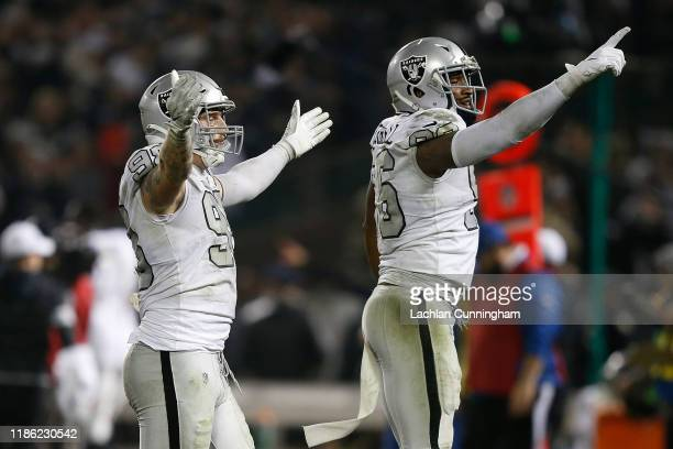 Maxx Crosby and Clelin Ferrell of the Oakland Raiders celebrate after an interception was thrown by Philip Rivers of the Los Angeles Chargers late in...