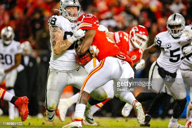 Maxx Crosby of the Oakland Raiders tackles Darwin Thompson of the Kansas City Chiefs for a loss in the fourth quarter at Arrowhead Stadium on...