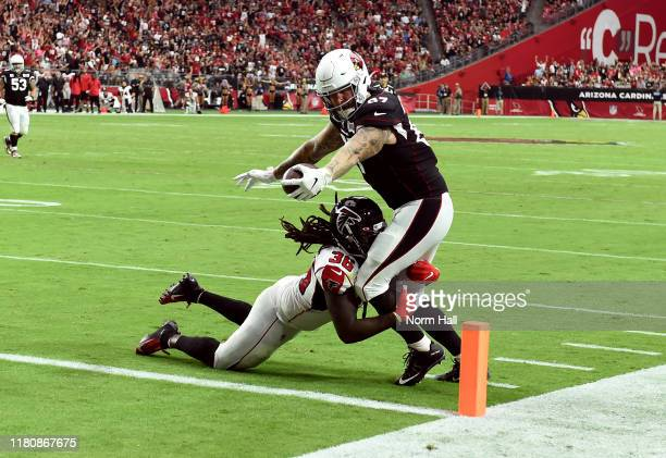 Maxx Williams of the Arizona Cardinals stretches the ball over the goal line for a touchdown while being tackled by Kemal Ishmael of the Atlanta...