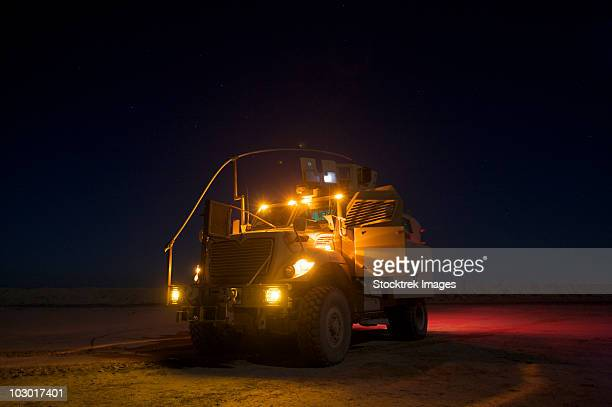 A MaxxPro Mine Resistant Ambush Protected (MRAP) vehicle with running lights on at night.
